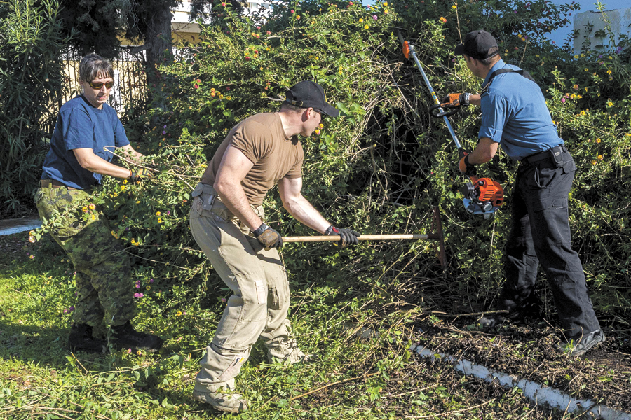 Crew members from HMCS Charlottetown spread some holiday cheer by helping to clean the grounds of an orphanage in Chania, Greece, during Operation Reassurance. Photos by Cpl Blaine Sewell, Formation Imagery Services