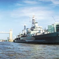 HMS Belfast alongside in the River Thames with Tower Bridge in the background.