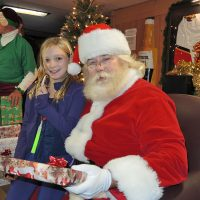 Santa Clause hands out a present to one delighted party goer. Photo by Peter Mallett, Lookout