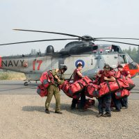 Members of the British Columbia Forest Service pick up their bags after being dropped off by a Sea King in support of OP LENTUS Aug. 21. Photo by Cpl Jeffrey Clement