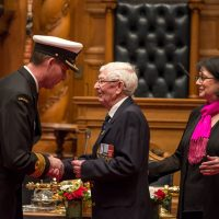 MS (Retired) John Wood shakes hands with Capt(N) Julian Elbourne after receiving a Special Service Medal and Canadian Peacekeeping Service Medal from Lieutenant Governor of B.C. Janet Austin. Photo by Stephanie Raymond