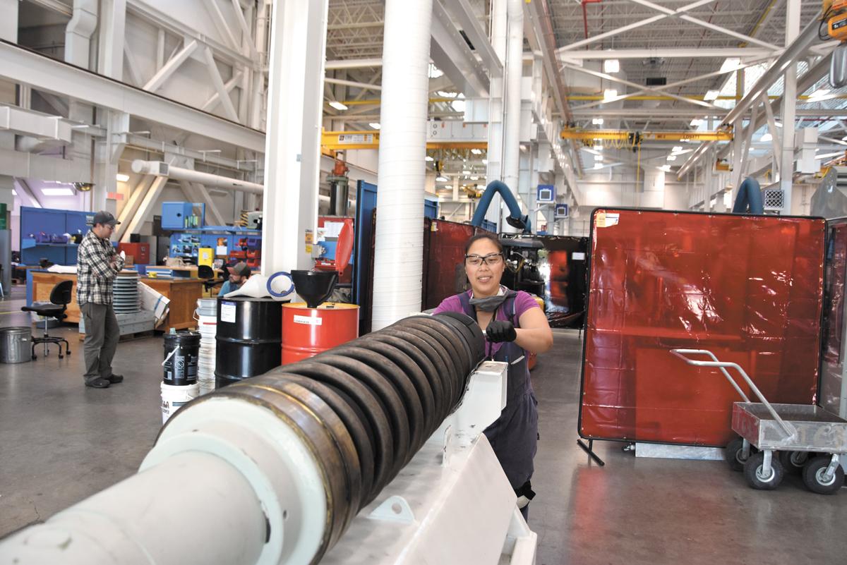 Antoniette Yap, a millwright apprentice at Fleet Maintenance Facility Cape Breton, cleans the 57mm barrel of HMCS Winnipeg's main gun while conducting an inspection of naval ordnance.