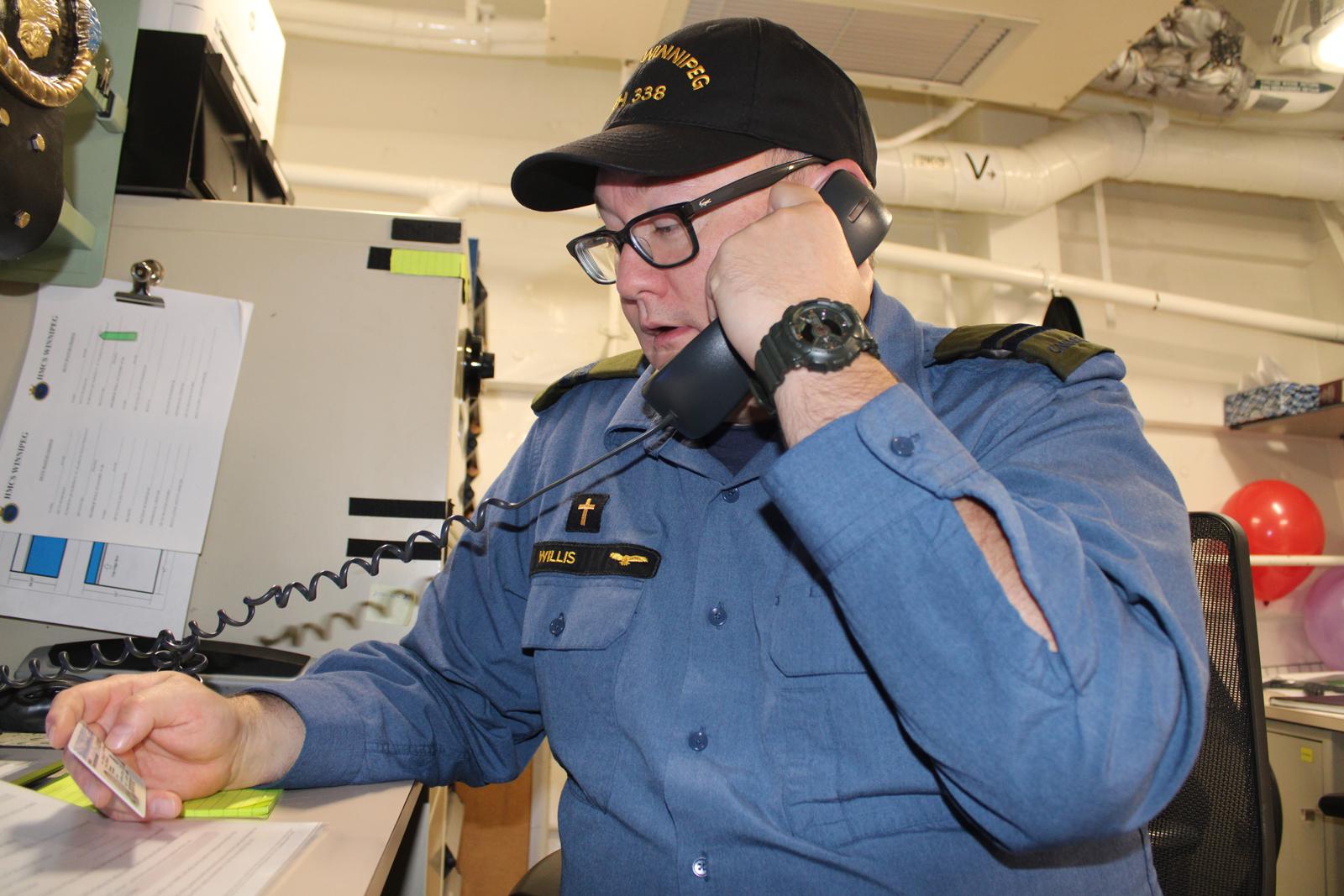Capt Chris Willis, HMCS Winnipeg's Padre, casts his vote in the provincial election via phone.