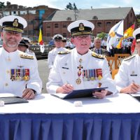 Image by LS Zachariah Stopa, MARPAC Imaging Services Rear Admiral Bill Truelove, outgoing Commander Maritime Forces Pacific (MARPAC), Vice Admiral Mark Norman, Commander Royal Canadian Navy and Rear Admiral Gilles Couturier, incoming Commander MARPAC, sign the change of command certificates during the Change of Command ceremony July 14.
