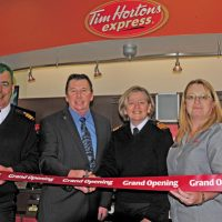 Peter Mallett, Lookout From left: Cdr Wes Golden, CANEX vice president Mack McMillan, Cdr Brigitte Boutin, and CANEX Express Mart manager Iris Shiplack cut the ribbon during the grand opening ceremony of a Tim Horton's express at their Colwood outlet.