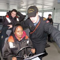 "A/SLt Matthew Heim of HMCS Malahat shows Sara Geday how to ""drive"" a 33-metre Orca-class vessel."