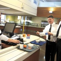 Base Commander, Captain (N) Steve Waddell tries the new debit and credit card payment options at Nelles with the assistance of Food Service Attendant Leah Stewart. CPO1 Gino Spinelli, Base Chief Petty Officer, stands next in line.