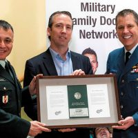 Brigadier-General Nicolas Eldaoud and Colonel Dan Harris present the Military Family Coin to Scott Murray during the launch of the Calian Military Family Doctor Network at Toronto's Military Family Resource Centre Jan. 20.