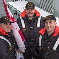 Crew members from HMCS OTTAWA, Able Seaman Marotte (left), Ordinary Seaman Moore (center), and Ordinary Seaman Thompson (right) prepare to hoist flags on the ship's Flag Deck during preparations to depart Esquimalt Harbour for the first time following the frigate's Halifax Class Modernization Project refit.