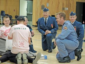 "Robert ""Scratch"" Mitchell, a retired Lieutenant-Colonel who served for 20 years in Canada's Air Force, looks on during a first aid demonstration by the 848 Royal Roads Royal Canadian Air Cadet Squadron during their 39th annual Ceremonial Review at Belmont Secondary School in Langford. Bottom left: Mitchell inspects members of the Squadron."