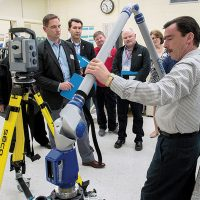 Dan Ouellette, group leader of Quality Engineering Test  Establishment, Measurement Sciences in Ottawa, demonstrates the movement of an articulating arm Coordinate Measurement Machine, which is used for both contact (tactile probing/scanning with a stylus), and non-contact scanning using a laser accessory at the recent Open House. Photo by DND