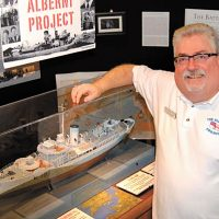 Lewis Bartholomew, Founder and Director of HMCS Alberni Museum and Alberni Project stands proudly next to a model of HMCS Alberni.