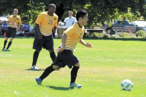 It's a race to the ball between CFB Esquimalt and CFB Comox players. Photos by Rachel Lallouz, Lookout