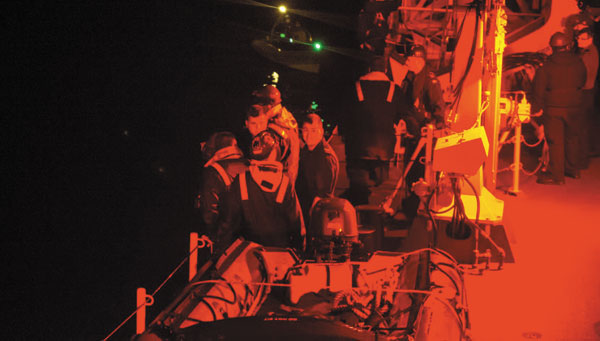 The crew of HMCS Ottawa watch from the deck as two men aboard a burning fishing boat Sherry C are rescued by personnel in a rigged-hulled inflatible boat.