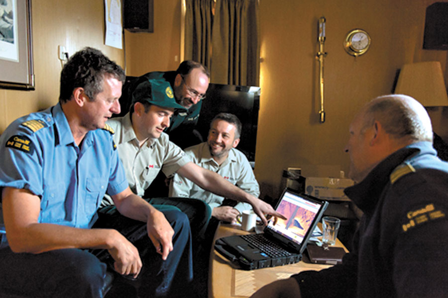 Canadian Coast Guard Ship Sir Wilfrid Laurier's Commanding Officer Bill Noon (left),  and Parks Canada's Ryan Harris (second from left), show the side-scan sonar image of the wreck to Marc-André Bernier (third from left), Jonathan Moore (fourth from left), and Chief Officer Rich Marriott (at far right). Photo by Theresa Nichols, Fisheries and Oceans Canada