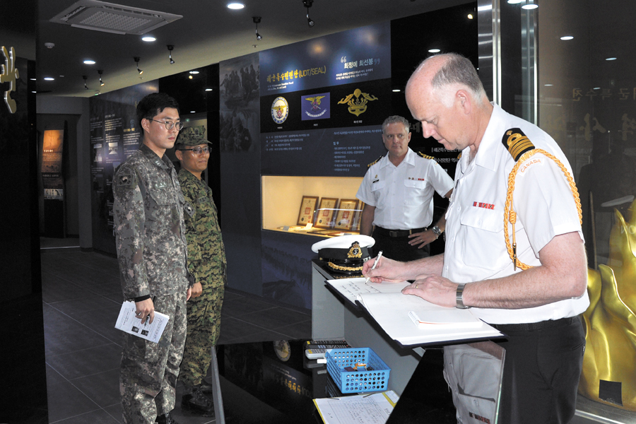 Capt(N) James Cotter, Canadian Defence Attaché, signs the guestbook at the museum.