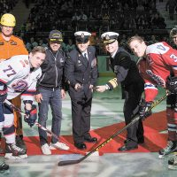 Rear Admiral Art  McDonald, Commander Maritime Forces Pacific, and Chief Petty Officer First Class Gilles Grégoire, Formation Chief Petty Officer, ready for the ceremonial puck drop between Adam Brooks, Captain of the Regina Pats, and Ryan Gagnon, Captain of the Victoria Royals, at centre ice.