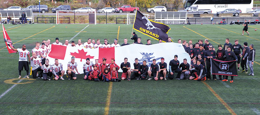 Touch football teams representing HMCS Calgary, dressed in white (left), and HMCS Ottawa, dressed in black (right) gather for a group photograph ahead of their pre-Grey Cup game. Photo by LS Ogle Henry, MARPAC Imaging Services