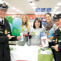 "Capt(N) Steve Waddell and CPO1 Gino Spinelli joined CANEX staff Tracy Horner and Sara Johnson, and Health Promotion's Allie Jones in handing out healthy food choices to patrons of Naden's CANEX outlet Jan. 11. The food items are now labelled with ""Benefit"" identifiers as part of a new healthy food program at the retail store. Photo: Peter Mallett, Lookout Newspaper"