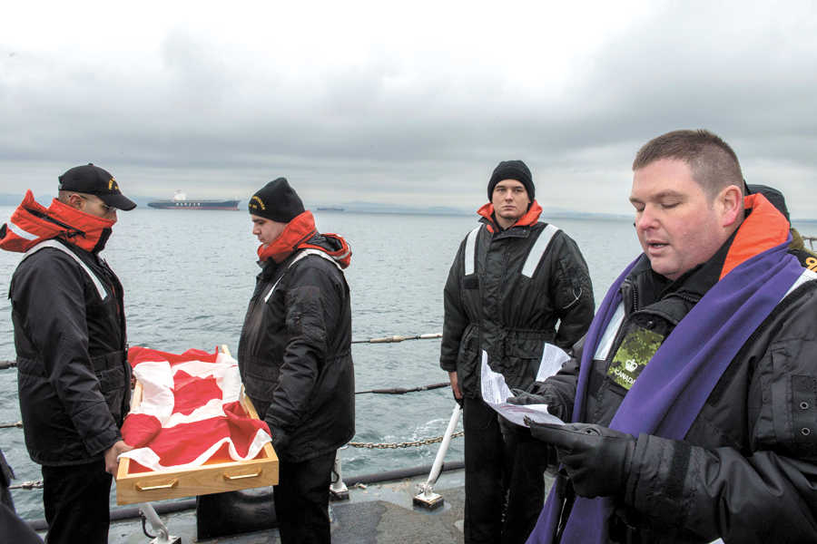 Major Mike Gibbons (right), Senior Fleet Chaplain, says a prayer as he conducts a burial at sea ceremony prior to the ashes being committed to the sea. Photos by MCpl Brent Kenny, MARPAC Imaging Services
