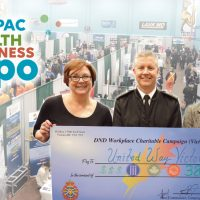 Rear-Admiral Art McDonald, Commander Maritime Forces Pacific (MARPAC), presents a $385,000 cheque to Eileen Dooley of HealthPartners Canada and United Way of Greater Victoria CEO, Patricia Jelinski at the MARPAC Health and Wellness Expo at the Naden Athletic Centre, Feb. 16.
