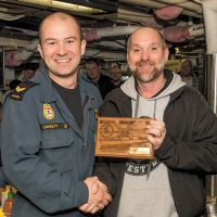 LS Matt Corbett, a hull technician in Athabaskan, was presented the plaque from the ship's Junior Rank Mess by CPO1 Fred McCrea, who came back to his former ship for the final day sail on Feb. 8. Photo by Cpl Tony Chand, FIS Halifax