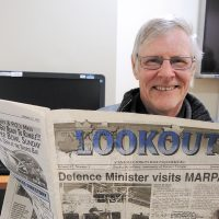 Lloyd Mathews, former FMF Weapons Shop worker, displays a Jan. 15, 1997, issue of the Lookout newspaper that he buried in a time capsule along with other items. Photo by Peter Mallett, Lookout Newspaper
