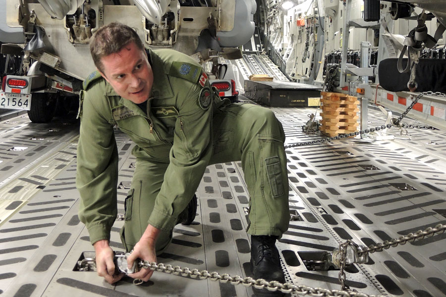 MWO Dave Daly, a Loadmaster with 429 Transport Squadron in Trenton, Ont., secures a RHIB to the floor of a C-17 Globemaster cargo plane. Photo by Peter Mallett/Lookout