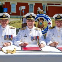 (Centre) Rear-Admiral Art McDonald, Commander Maritime Forces Pacific; former Base Commander Commodore Steve Waddell (left); and incoming Base Commander Captain (Navy) Jason Boyd (right), sign off on papers officially appointing Capt(N) Boyd to his new post during a Change of Command Ceremony at Museum Square, June 22.