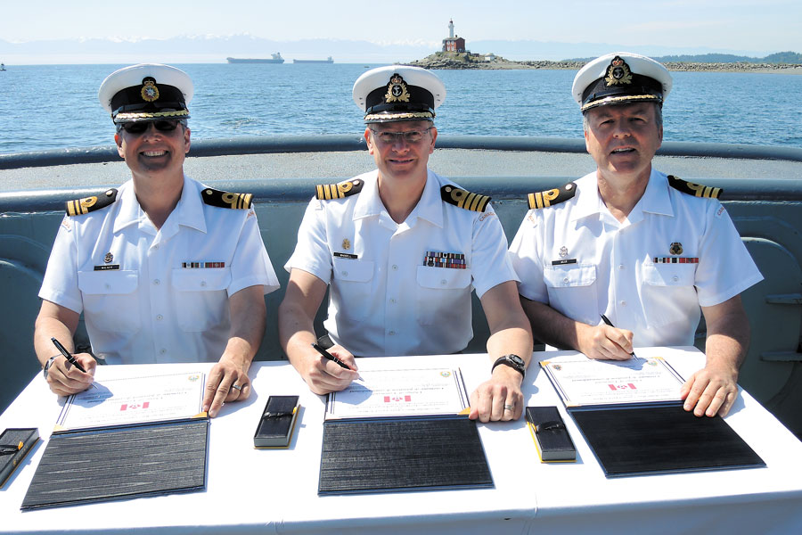 Base Commander Capt(N) Steve Waddell, center, signs the change of command certificates that officialises passing command of Port Operations and Emergency Services from outgoing Cdr Andrew Muir to incoming Cdr Greg Walker. Photos by Peter Mallett, Lookout Newspaper