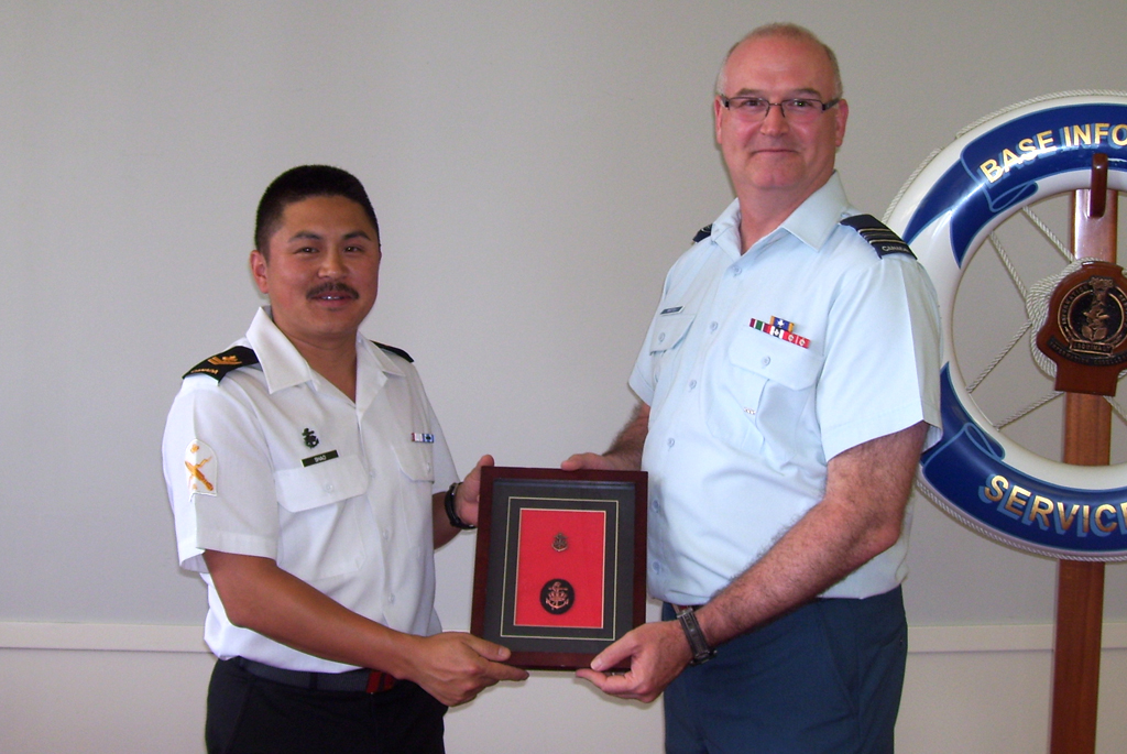 MS Timothy Shao receives the Bronze Level Sea Service Insignia from Maj Grant Whittla.