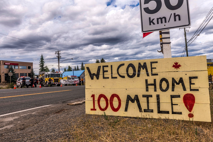 Firefighters and emergency workers line the highway to greet local citizens following the rescinding of the fire evacuation order in 100 Mile House, B.C.