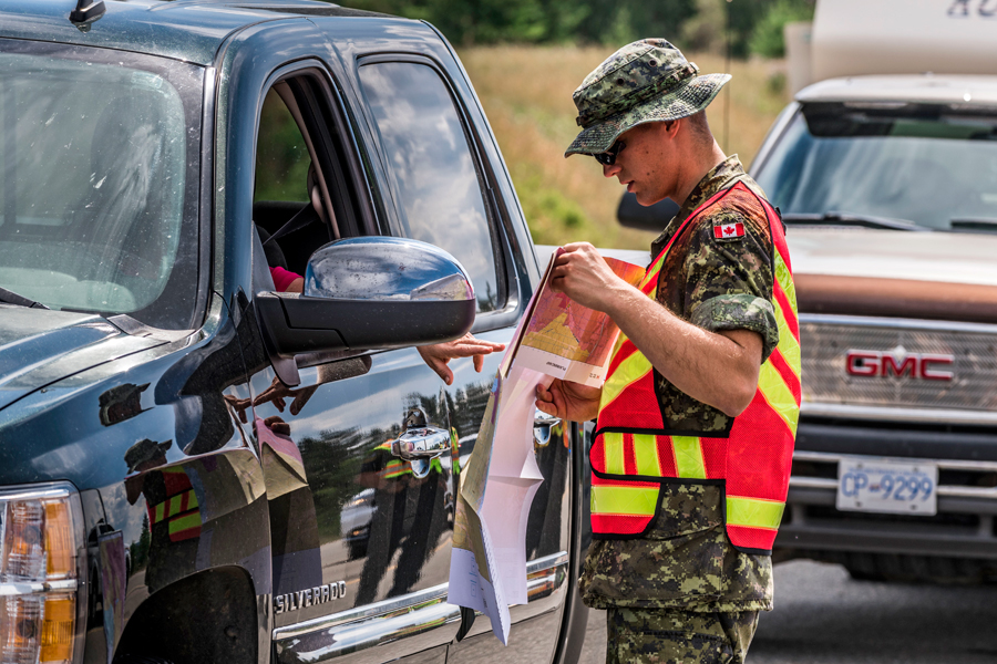 A member of Land Task Force - Pacific shows a returning resident of Williams Lake, B.C., the evacuation alert and order areas during Operation Lentus. Photo by MCpl Malcolm Byers, Wainwright Garrison Imaging