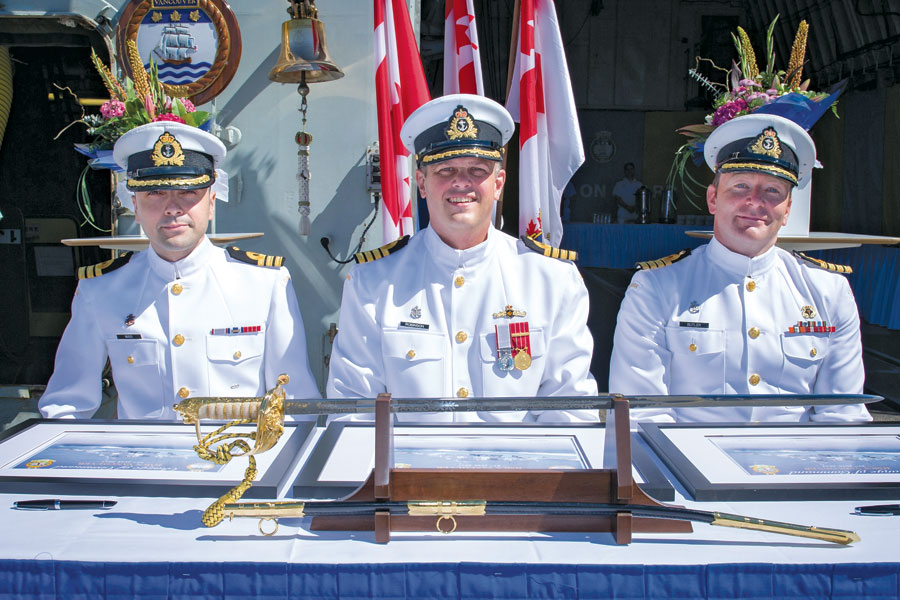Reviewing Officer, Capt(N) Christopher Robinson (centre), signs the certificate officiating the command change between Outgoing Commanding Officer, Capt(N) Clive Butler (right), and the Incoming Commanding Officer, Cdr Christopher Nucci (left). Photo by LS Valerie LeClair, MARPAC Imaging Services