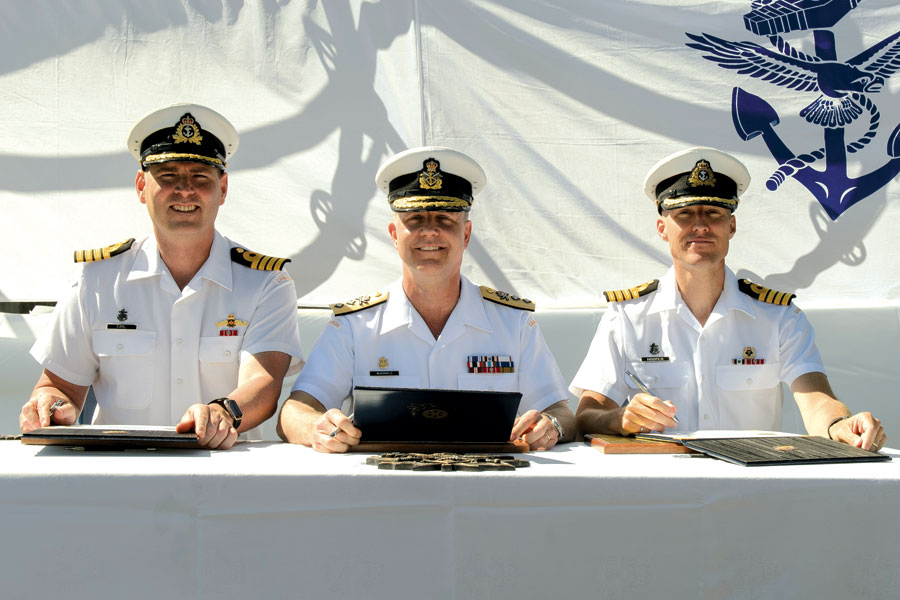From left to right: Outgoing Commanding Officer, Captain (Navy) Christopher Earl; Commander Maritime Forces Pacific, Rear Admiral Art McDonald; and Incoming Commanding Officer, Captain (Navy) Ed Hooper sign transfer of command certificates. Photo by Cpl Blaine Sewell, MARPAC Imaging Services