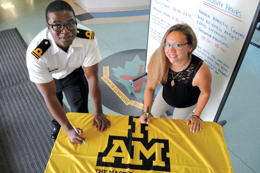 SLt Tawonga Mkanda (left), a Deputy Base Personnel Services Officer at Base Administration, and Amy Lee, Administrative Assistant at Base Administration, sign their names and words of encouragement on the Invictus Games flag at the Naden Athletic Centre. Photo by Peter Mallett, Lookout Newspaper
