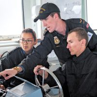 Two candidates for the Raven Program, OS Nicole Kununak (left) and OS Sam Seven Deers (right), receive maneuvering instructions from AB Nathaniel Lewis, during the day sail on Aug. 14. Photo by LS David Gariepy, MARPAC Imaging Services