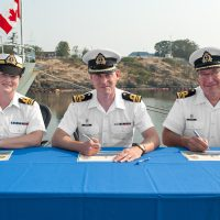 Reviewing Officer, LCdr Lucas Kenward (centre), signs the certificate officiating the command change between Outgoing Commanding Officer, LCdr Todd J. Bacon (right), and the Incoming Commanding Officer, LCdr Kristina Gray (left). Photos by LS David Gariepy, MARPAC Imaging Services