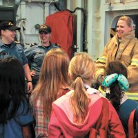 LS Corey Aube from HMCS Halifax talks about some of her firefighting gear with the visiting Girl Guides group. Photos by Ryan Melanson, Trident Staff
