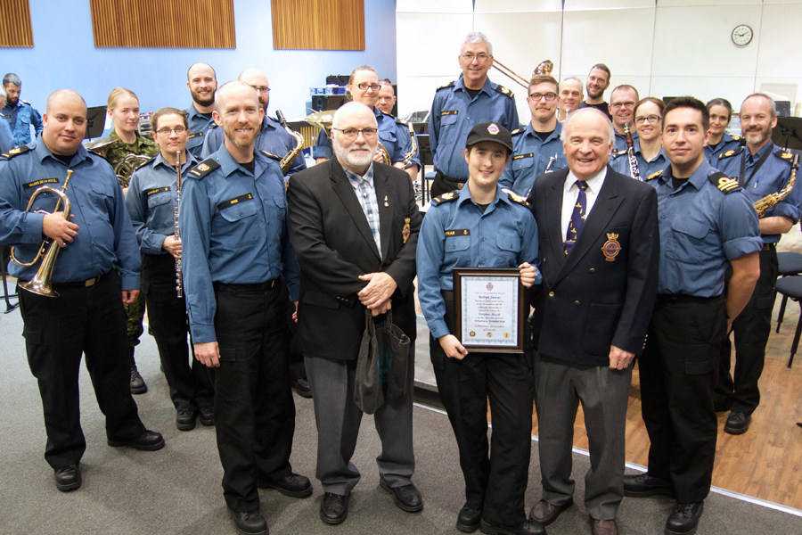 Naden Band composer and saxophonist Petty Officer Second Class Robyn Jutras (centre) is joined by fellow band members as she is presented an honorary membership in the Submariners Association of Canada (SAOC) by SAOC Canada West President, Lloyd Barnes (right) and past president Paul Hansen. The two former RCN submariners dropped by the band headquarters Nov. 21 to show their appreciation to PO2 Jutras for composing an official SAOC march entitled The Dolphin March. Photo by Peter Mallett, Lookout Newspaper