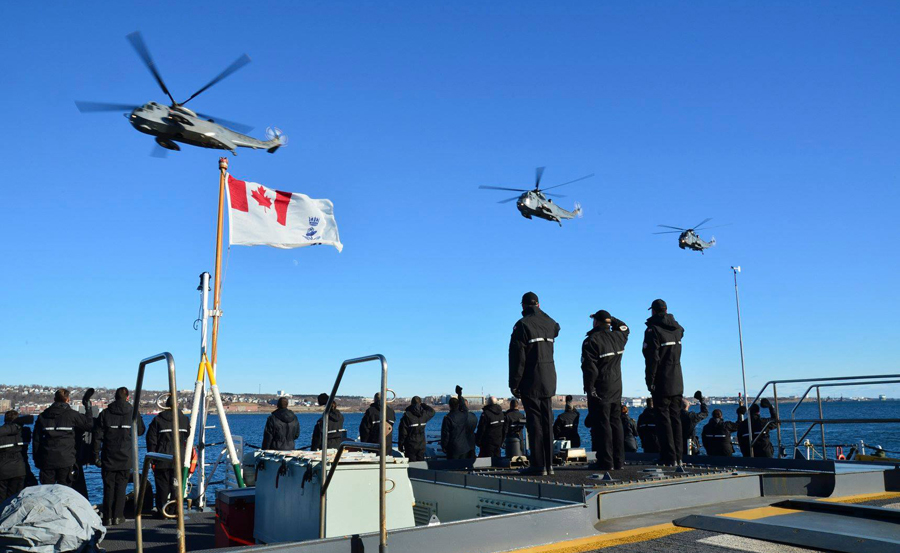 Royal Canadian Navy personnel wave and salute as 423 Maritime Helicopter Squadron conducts its final flight with CH-124 Sea King helicopters over Halifax Harbour Jan. 26. Photo by DND