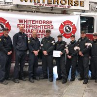 The team representing HMCS Whitehorse donates their $250 prize to the Whitehorse Firefighters Charitable Society.