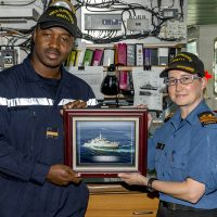 Sub-Lieutenant Lassina Traoré, left, a member of the Ivory Coast Navy, receives a framed photograph of HMCS Summerside from Commanding Officer Lieutenant-Commander Emily Lambert, to remind him of his time as an exchange officer aboard the ship. Photo by OS John Iglesias