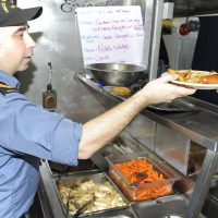 The Chief Cook of HMCS Whitehorse serves perogies and sausage to the crew. Photo by Lt (N) Paul Pendergast, Canadian Joint Operations Command Public Affairs Officer