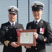 Commander Blair Saltel, HMCS Calgary Commanding Officer, presents Petty Officer First Class Kai Tin with his Chief Engineering Level 4 certificate. Photo by Peter Mallett, Lookout