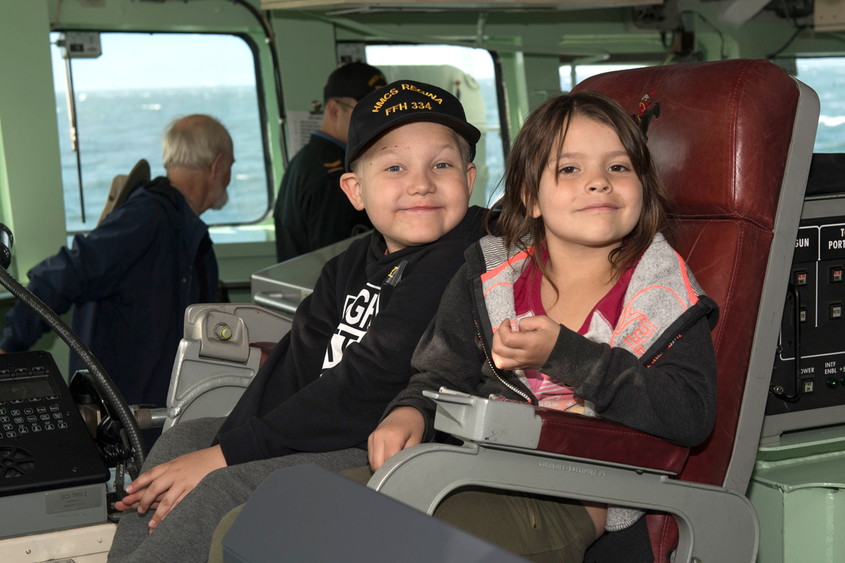 Trey Stylez Bruneau (left) and Clara Issel (right), members of the Chris Knox Foundation, sit in the Executive Officer's chair on the bridge of HMCS Regina May 31 during a day sail at sea. Photo by LS Mike Goluboff, MARPAC Imaging Services