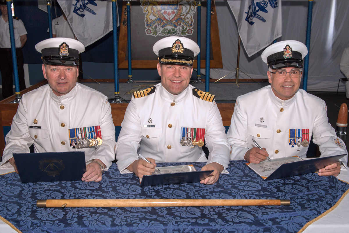 Change of Appointment for Base Chief, from the left: CPO1 Gino Spinelli, outgoing Base Chief; Capt(N) Jason Boyd, Base Commander, and CPO1 Ian Kelly, incoming Base Chief, sign the certificates officiating the transfer of appointment. Photo by LS Mike Goluboff, MARPAC Imaging Services