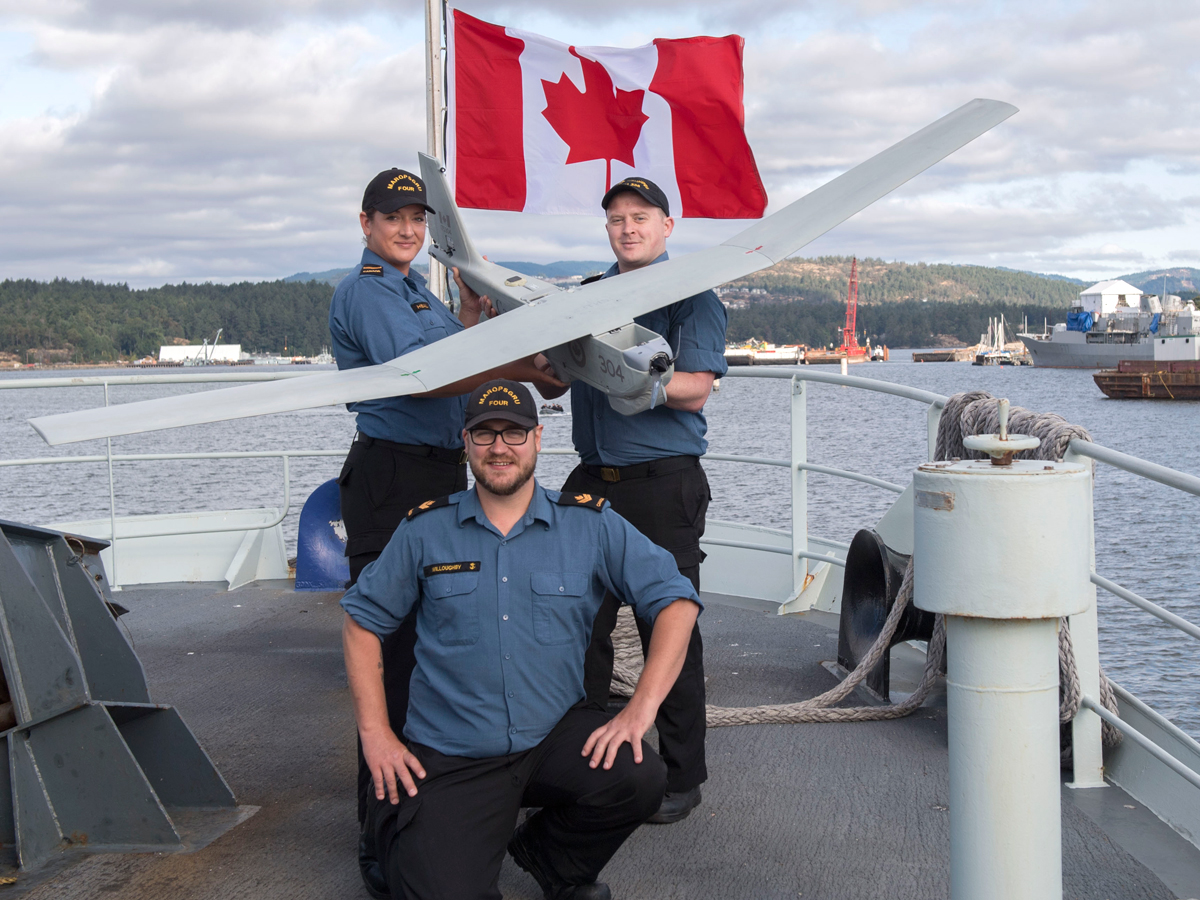 Left to right: Leading Seaman Meghan Heal, Master Seaman James Willoughby and Leading Seaman Erik Stirler showcase the Royal Canadian Navy's new Maritime Miniature Unmanned Aerial System, a CU-175 PUMA. Photo was taken on the fo'c'sle on board HMCS Edmonton Aug. 2. Photo by LS Mike Goluboff, MARPAC Imaging Services