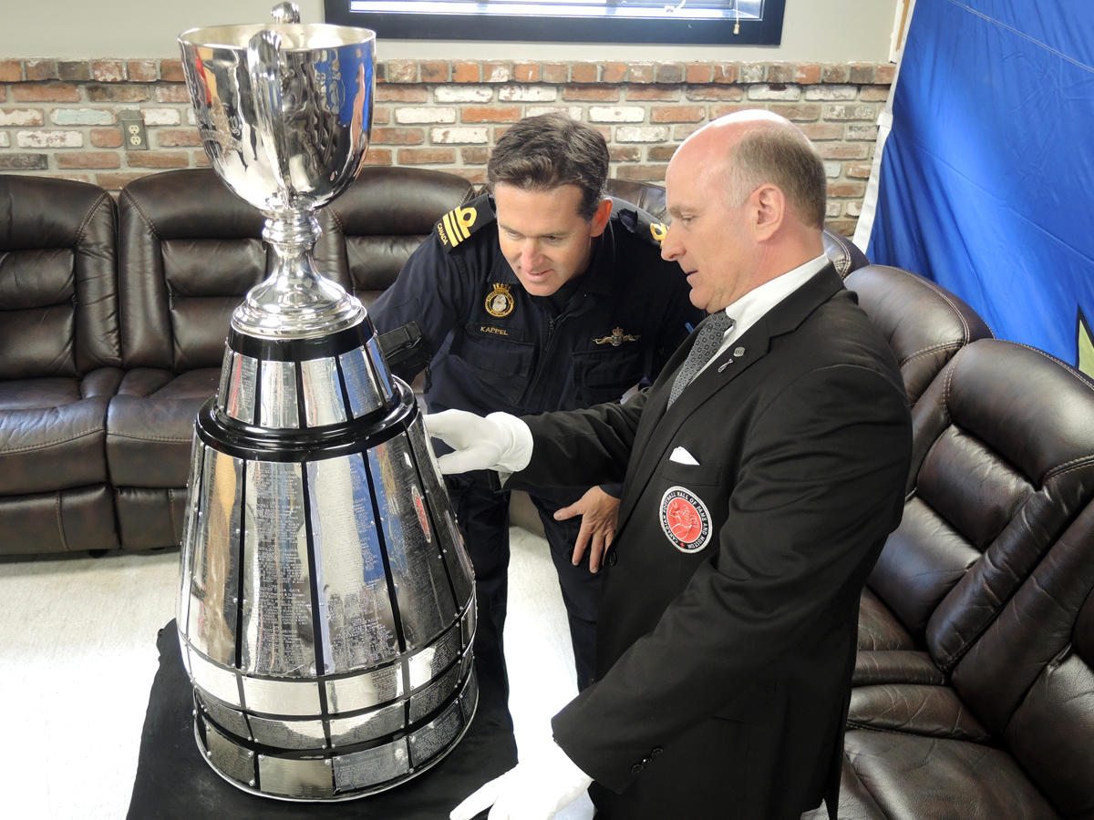Commanding Officer Fleet Diving Unit (Pacific), LCdr Rick Kappel and Grey Cup trophy handler Jeff McWhinney of the Canadian Football Hall of Fame inspect the trophy and its engraved panels of Grey Cup winners. Photo by Peter Mallet, Lookout