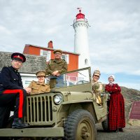 Fort Rodd Hill and Fisgard Lighthouse National Historic Sites interpreters in a 1942 Willys Jeep, in front of Fisgard Lighthouse. Photo by Fritz Mueller, Parks Canada